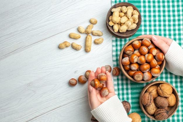 Вид сверху свежего сырого фундука с арахисом и грецкими орехами на белом столе