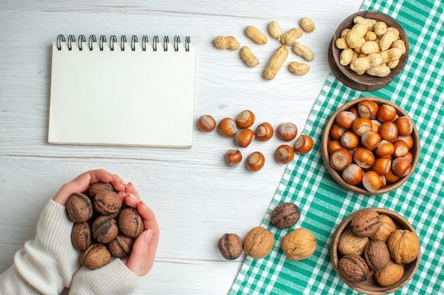 上面図白いテーブルにピーナッツとクルミと新鮮な生のヘーゼルナッツ