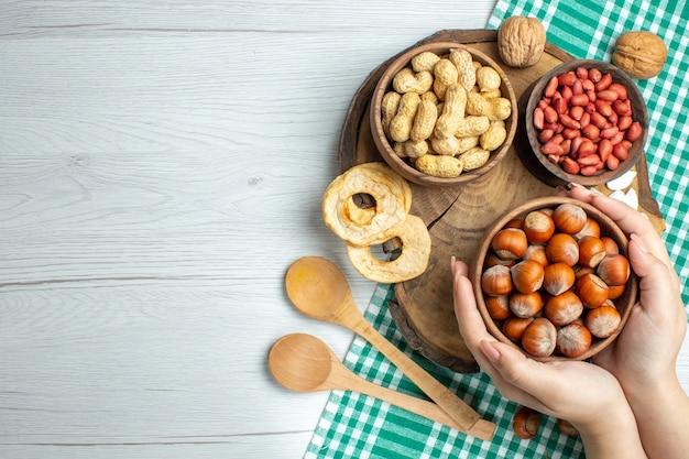 Вид сверху свежего сырого фундука с арахисом на белом столе