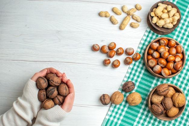 Vista dall'alto nocciole crude fresche con arachidi e noci sul tavolo bianco