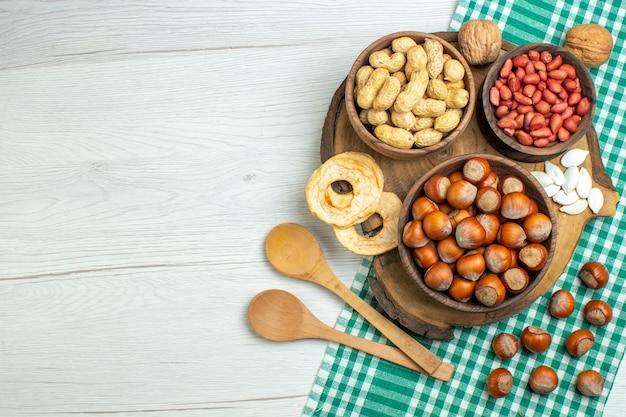 Nocciole crude fresche di vista superiore con le arachidi sulla noce di film dello spuntino dell'alimento della pianta del dado della tavola bianca