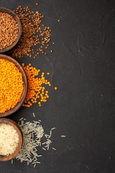 Top view fresh raw lentil with buckwheat on dark desk