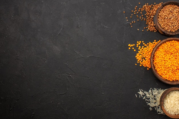 Vista dall'alto lenticchie crude fresche con grano saraceno sullo spazio buio