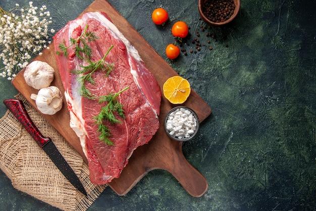Vista dall'alto di carni rosse crude fresche, aglio verde, sale al limone su tagliere di legno marrone, coltello su asciugamano di colore nudo, pomodori, pepe su sfondo di colore scuro
