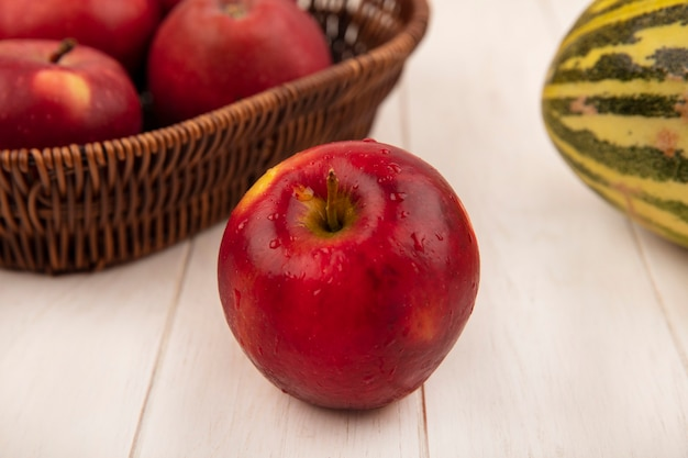 Top view of a fresh red apple with apples on a bucket with cantaloupe melon on a white wooden surface