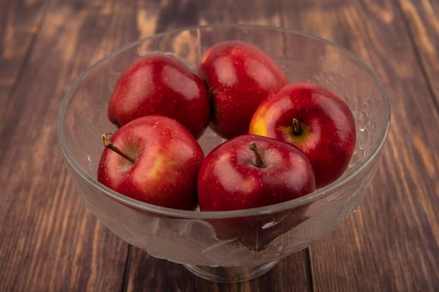 Vista dall'alto di mele rosse fresche su una ciotola di frutta trasparente su una superficie di legno
