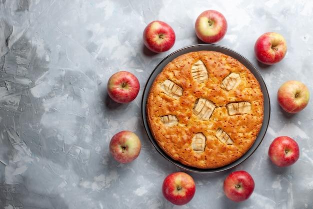 Mele rosse fresche di vista superiore che formano il cerchio con la torta di mele sulla vitamina matura pastosa fresca della frutta bianca del fondo