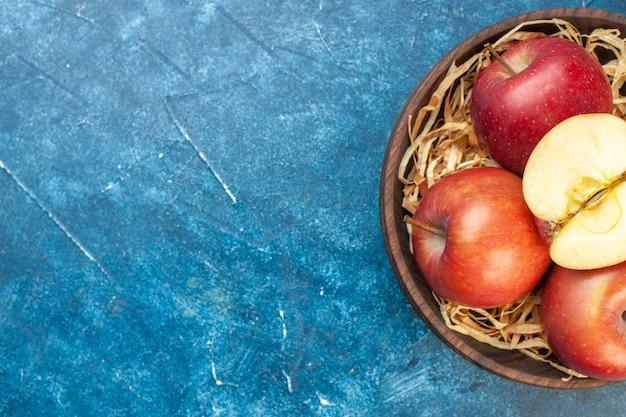 青いテーブルのプレート内の新鮮な赤いリンゴの上面図