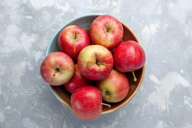 Вид сверху свежие красные яблоки внутри тарелки на белом фоне фрукты свежие спелые спелые витамины