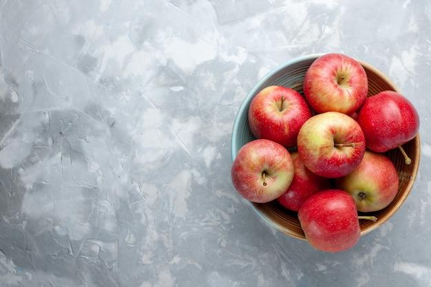 上面図白い背景の上のプレート内の新鮮な赤いリンゴフルーツ新鮮なまろやかな熟したビタミン