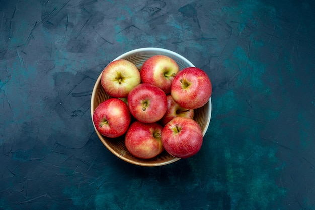 上面図濃い青の机の上のプレートのジューシーでまろやかな新鮮な赤いリンゴフルーツ新鮮な熟したまろやかなビタミン