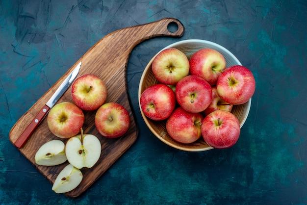 上面図新鮮な赤いリンゴジューシーでまろやかな内側のプレート、紺色の机の上にナイフでフルーツ新鮮な熟したまろやかなビタミン