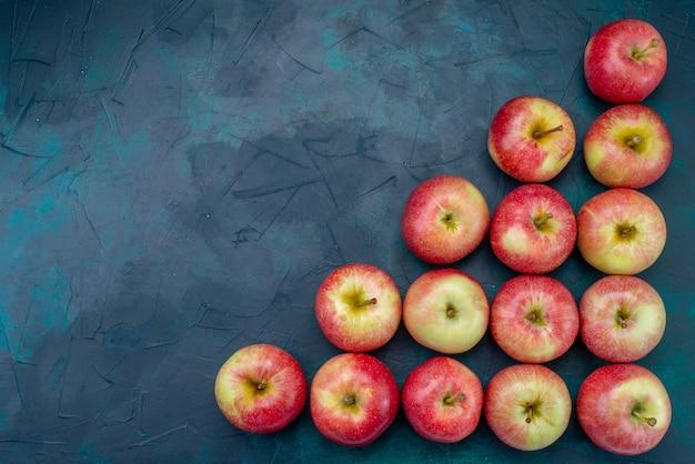 トップビュー新鮮な赤いリンゴジューシーでまろやかな紺色の背景に並ぶフルーツ新鮮な熟したまろやかなビタミン
