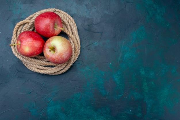 トップビュー新鮮な赤いリンゴジューシーでまろやかな紺色の背景熟した果実新鮮なビタミン
