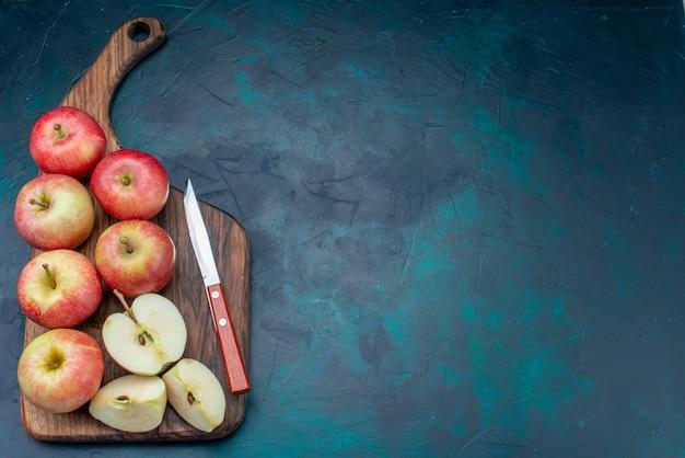 上面図新鮮な赤いリンゴジューシーでまろやかで、濃い青色の背景に茶色の机があります熟した果実新鮮なまろやかなビタミン