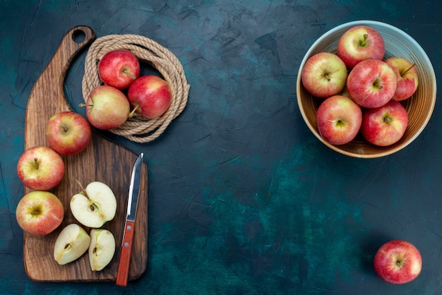 Vista dall'alto mele rosse fresche succose e pastose con scrivania marrone su sfondo blu scuro frutta matura fresca vitamina mellow