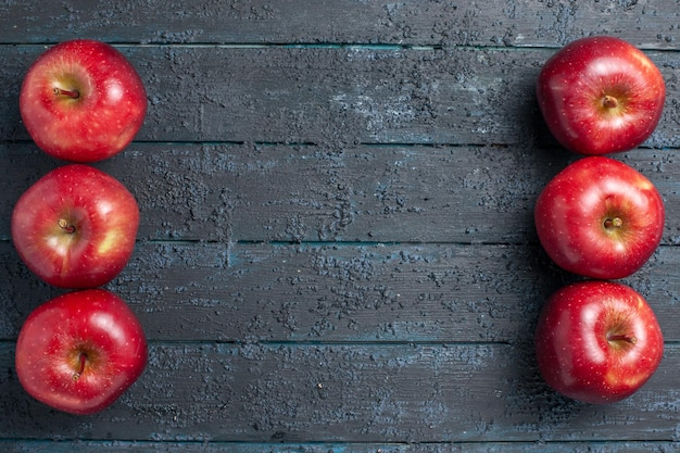 Вид сверху свежие красные яблоки спелые спелые фрукты на темно-синем столе цвет фруктов красный завод витамин свежий