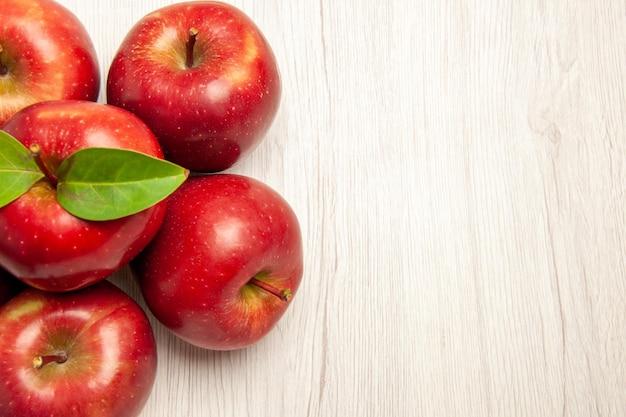 Вид сверху свежие красные яблоки, спелые и спелые фрукты на белом столе, фрукты, свежие цвета, многие растения, дерево