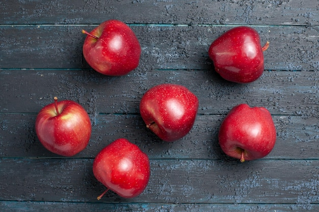 Vista dall'alto mele rosse fresche frutti dolci e maturi su scrivania blu scuro frutta colori interi pianta rossa vitamina fresca