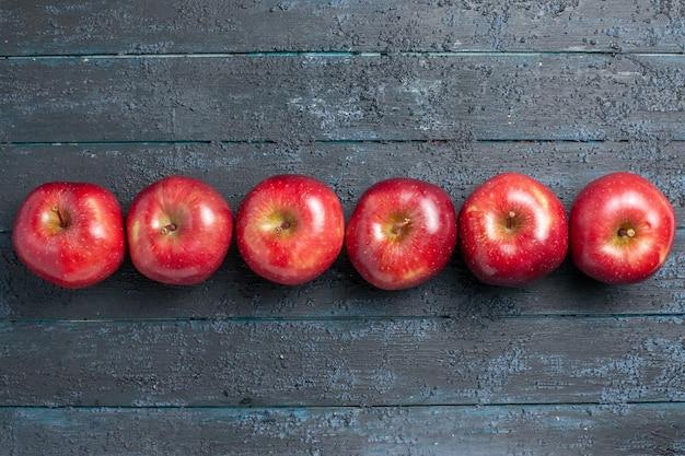 Вид сверху свежие красные яблоки, спелые и спелые фрукты, выложенные на темно-синем столе, много фруктов красного цвета, дерево, свежее растение