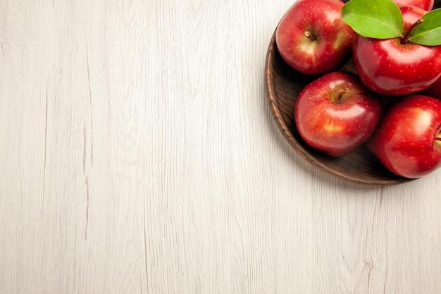 Вид сверху свежие красные яблоки, спелые и спелые фрукты на белом столе, фруктовое дерево, свежее растение, красный
