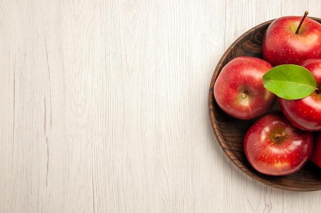 Вид сверху свежие красные яблоки, спелые и спелые фрукты на белом полу, фруктовое дерево красного цвета, свежее растение