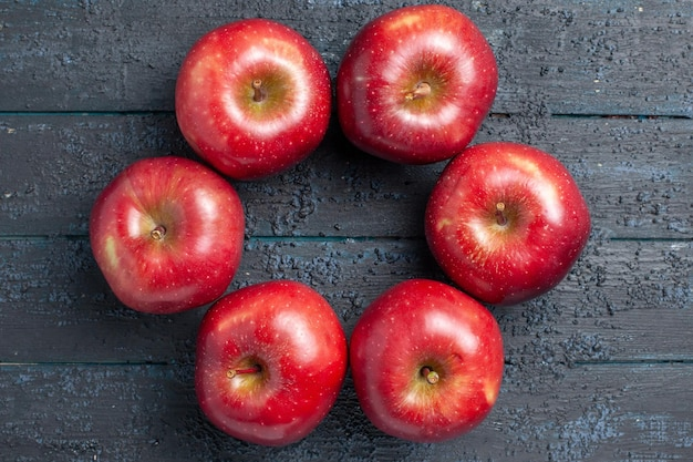 Top view fresh red apples ripe and mellow fruits lined on the dark-blue desk many fruit red color tree fresh plant