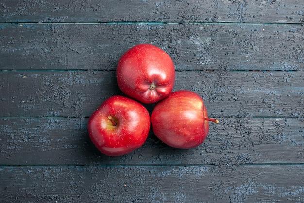 Vista dall'alto mele rosse fresche frutti maturi e morbidi allineati sulla scrivania blu scuro molti frutti rossi piante di alberi di colore fresco