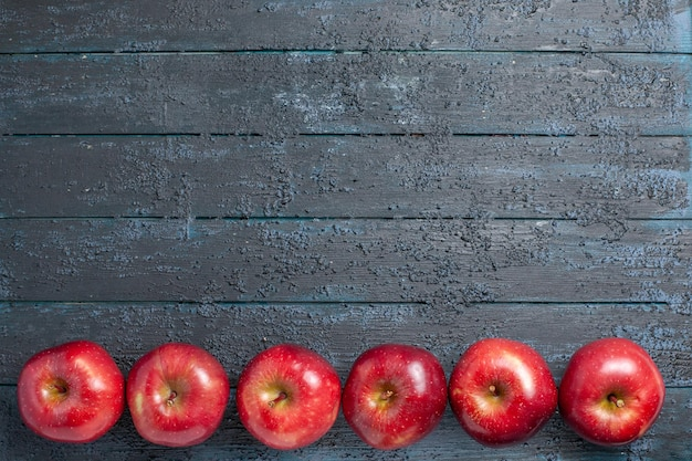 Top view fresh red apples ripe and mellow fruits lined on the dark blue desk many fruit red fresh color tree plant