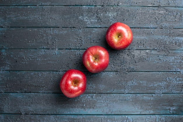 Top view fresh red apples ripe and mellow fruits lined on dark-blue desk many fruits red fresh plant color tree