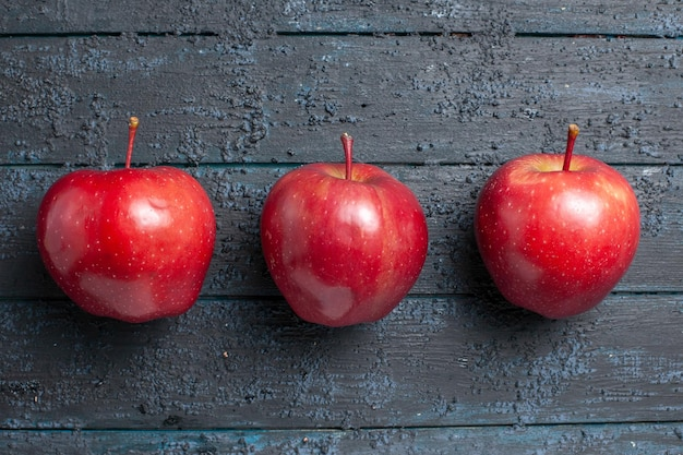 Top view fresh red apples ripe and mellow fruits lined on dark-blue floor many fruit red fresh plant color tree