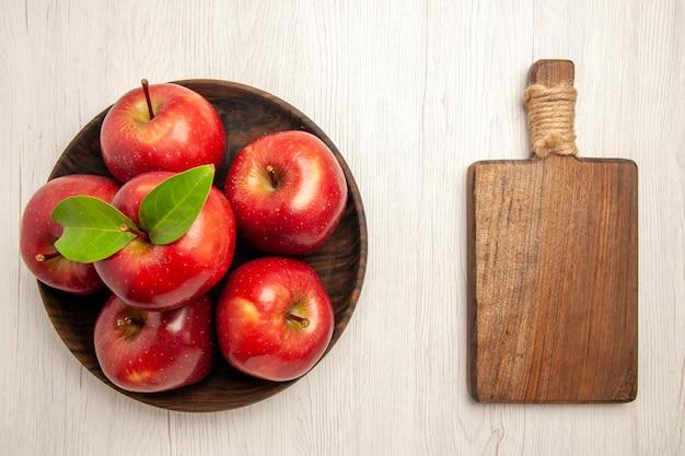 Vista dall'alto mele rosse fresche frutti maturi e morbidi sulla scrivania bianca frutta colori rossi albero pianta fresca