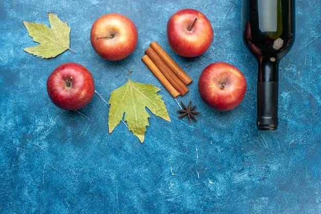 Vista dall'alto mele rosse fresche con una bottiglia di vino sull'albero della foto a colori dell'alcool della frutta matura della scrivania blu