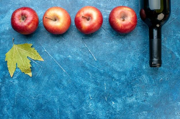 Vista dall'alto mele rosse fresche con bottiglia di vino sul tavolo blu albero foto a colori alcol frutta matura