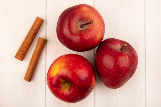 Vista dall'alto di mele rosse fresche con bastoncini di cannella isolato su una superficie di legno bianca