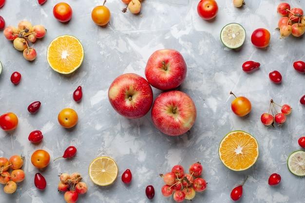 上面図白い机の上のレモンとチェリーと新鮮な赤いリンゴフルーツベリービタミン夏まろや