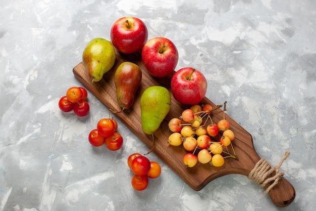 Вид сверху свежие красные яблоки с черешнями, сливами и грушами на светло-белом столе.