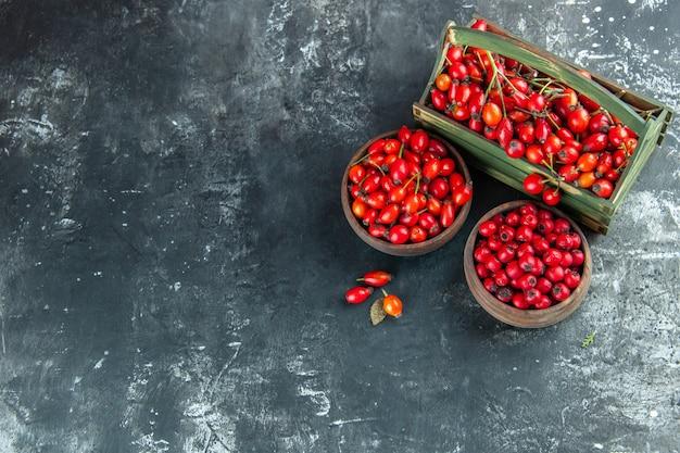 Vista dall'alto bacche rosse fresche sulla foto di frutta di colore selvatico della bacca di salute della scrivania in legno scuro