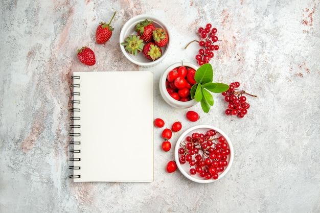 上面図白いテーブルにメモ帳付きの新鮮な赤いベリー赤いフルーツベリー新鮮な