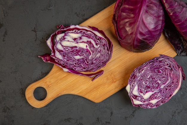 Top view of fresh red cabbage on a cutting wooden board on dark