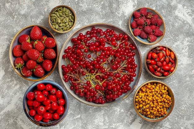 Вид сверху свежей красной клюквы с другими ягодами на белом фоне