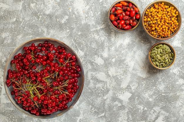 Vista dall'alto mirtilli rossi freschi con altri frutti su sfondo bianco
