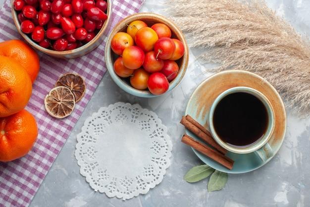 Top view fresh red dogwoods with tea on light desk fruit fresh tea mellow ripe