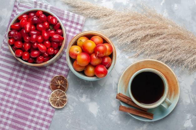 Вид сверху свежие красные кизилы с чаем на белом столе фруктовый свежий чай спелый