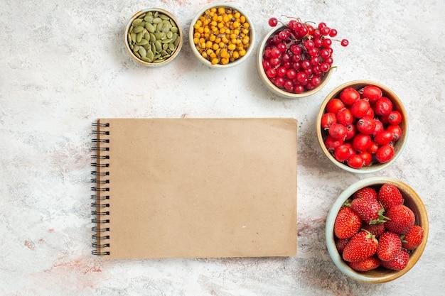 Vista dall'alto frutti rossi freschi sul tavolo bianco frutta colore fresco