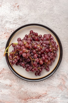Top view fresh red grapes juicy and mellow fruits inside plate on white surface