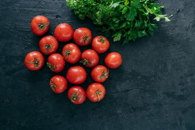 Top view of fresh red heirloom tomatoes and green parsley on black background.