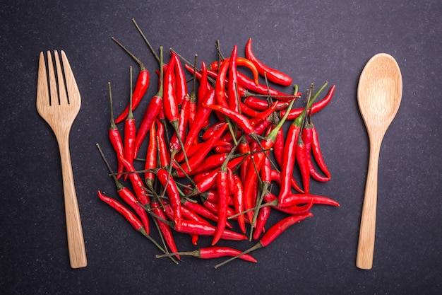 Top view fresh red hot chilli on black stone board