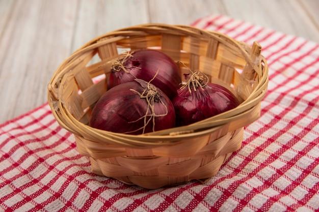 Vista dall'alto di cipolle rosse fresche su un secchio su un panno rosso controllato su una superficie di legno grigia