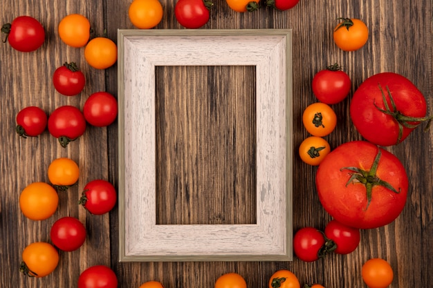 Vista dall'alto di pomodorini rossi e arancioni freschi isolati su una parete in legno con spazio di copia